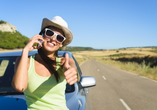 Successful happy woman on cellphone call enjoying summer car travel vacation and doing approval positive gesture with thumbs up. Female traveler on roadtrip in Spain.